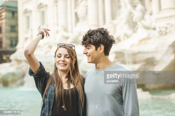 flipping a coin in trevi fountain - trevi fountain stock photos and pictures