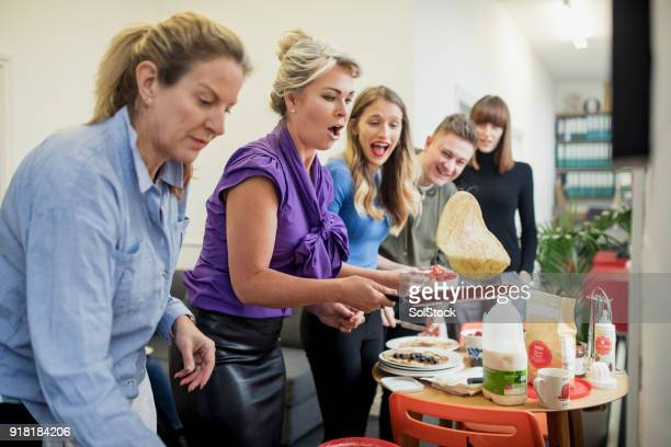 flipping pancakes in the office - pancake day stock pictures, royalty-free photos & images