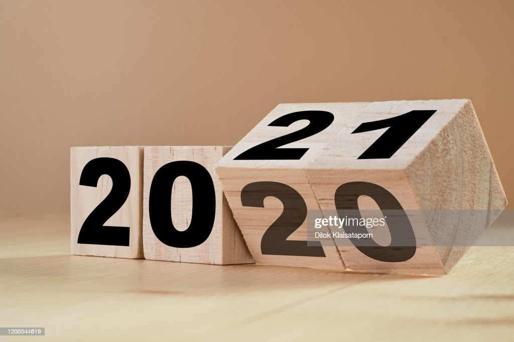 Flipping wooden cubes for new year change 2020 to 2021. New year change and starting concept. : Stock Photo
