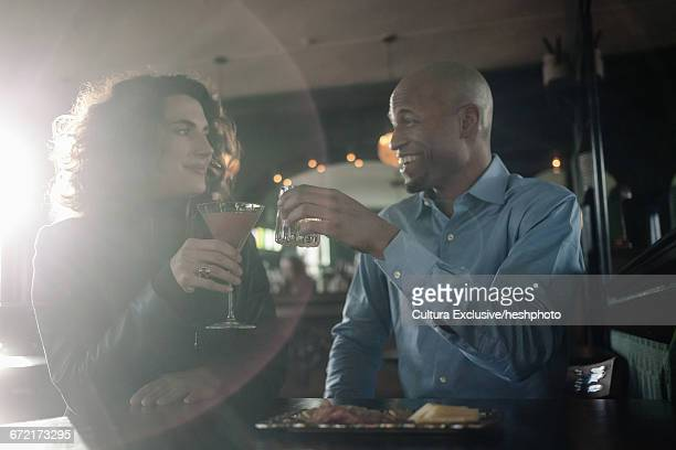 flirtatious man and woman raising a toast at recreational bar - heshphoto stock pictures, royalty-free photos & images