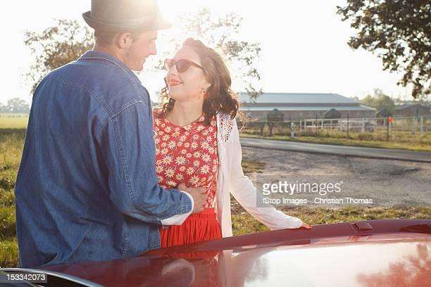 A flirtatious rockabilly couple standing next to a vintage car