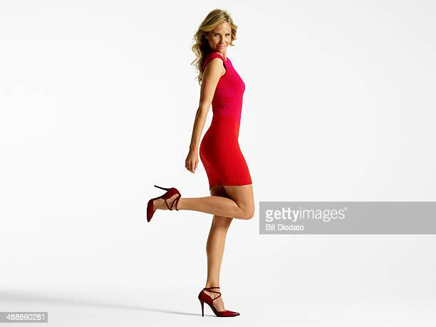 Flirtatious woman in red dress with one leg up