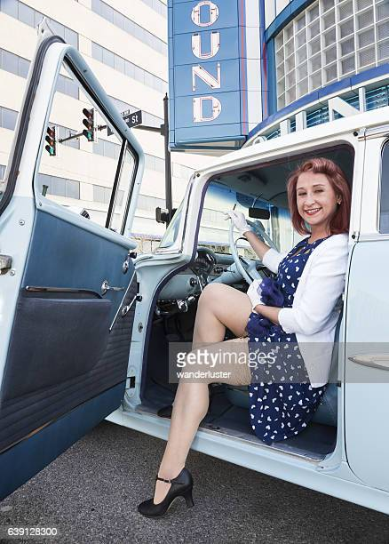 flirtatious young woman in vintage car - woman open legs stock photos and pictures