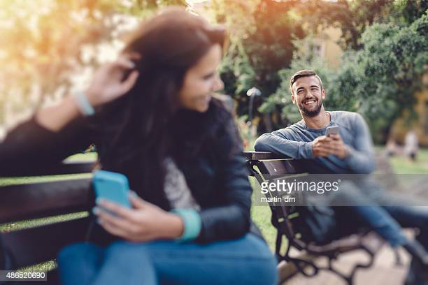 flirting couple in the park texting on smartphones - daten stockfoto's en -beelden