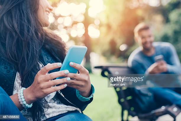 flirting couple in the park texting on smartphones - flirting stock pictures, royalty-free photos & images
