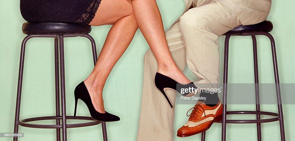 Flirting couple playing footsie : Stock Photo