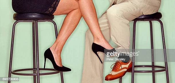 flirting couple playing footsie - may december romance stock photos and pictures
