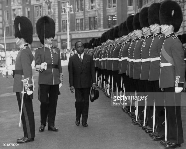 Félix HouphouëtBoigny President of the Côte d'Ivoire inspects a guard of honour of Coldstream Guards at Victoria Station at the end of his state...