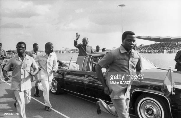 Félix HouphouëtBoigny saluant la foule depuis sa voiture lors des Jeux Universitaires de l'Afrique de l'Ouest à Yamoussoukro Côte dIvoire