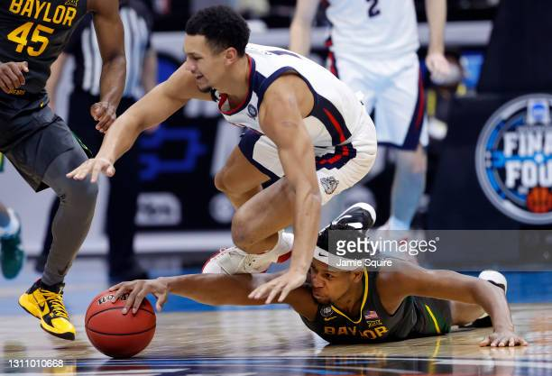 Flo Thamba of the Baylor Bears and Jalen Suggs of the Gonzaga Bulldogs dive for a loose ball in the National Championship game of the 2021 NCAA Men's...