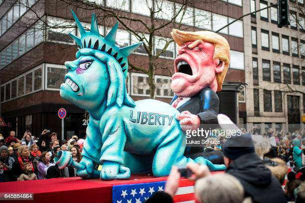 A float featuring US President Donald Trump and the Statue of Liberty drives in the annual Rose Monday parade on February 27 2017 in Dusseldorf...