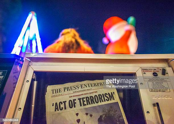 A float in the Redlands Christmas Parade passes by a newspaper rack with the Riverside Press Enterprise's front page from Saturday Redlands Christmas...