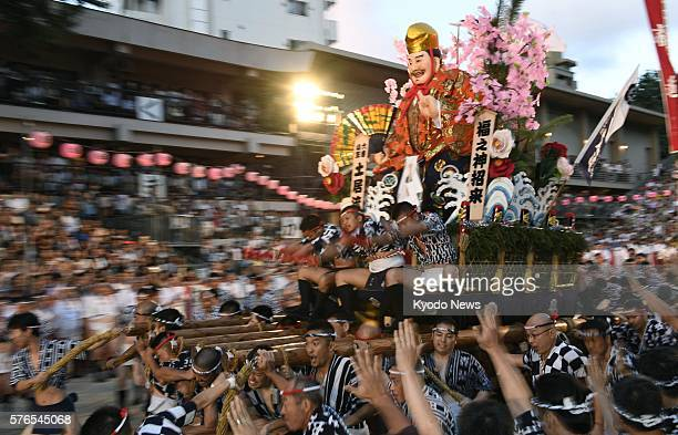 A float speeds through the compounds of Kushida Shrine during the Hakata Gion Yamakasa Festival in the southwestern Japan city of Fukuoka in the...