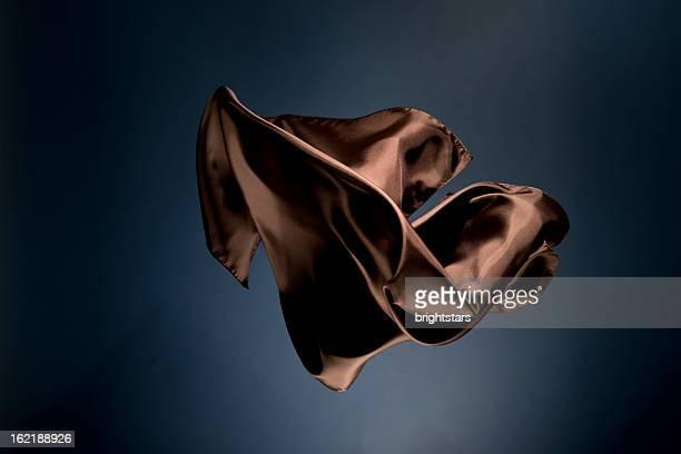 Floating brown satin on a dark blue background
