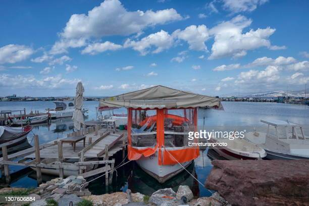 floating cafe with red cover at inciralti fishing marina. - emreturanphoto stock pictures, royalty-free photos & images