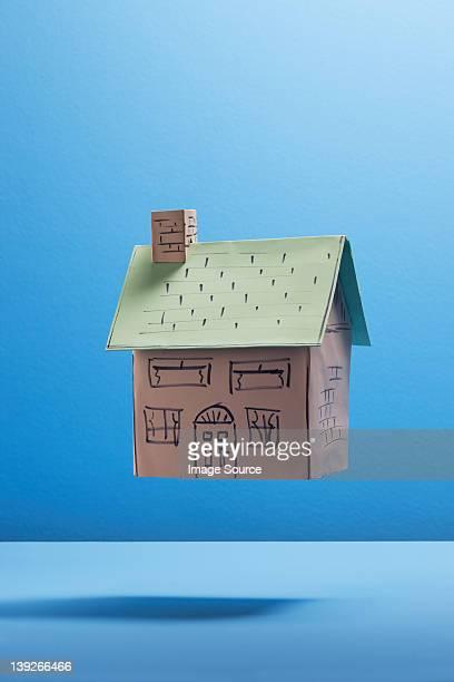 Schwimmende Papier Haus gegen blauen Hintergrund
