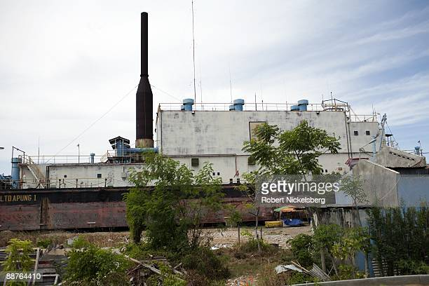 A floating generator barge lies aground in a Banda Aceh neighborhood after it ws carried 6 kms inland during the December 26 2004 tsunami disaster in...
