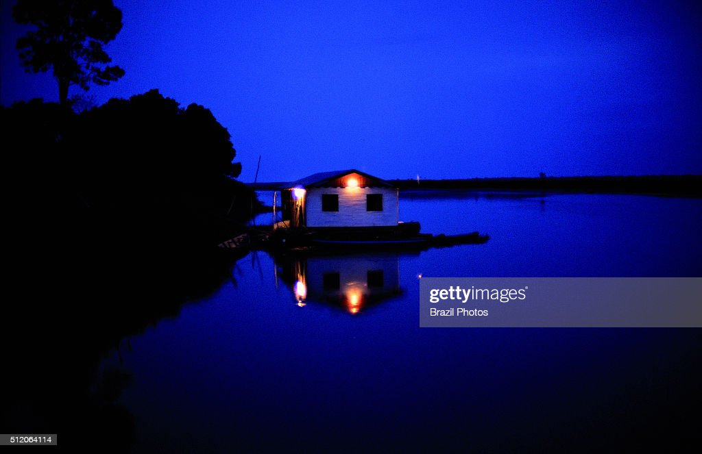 Floating house in Amazon rainforest at night, Brazil.