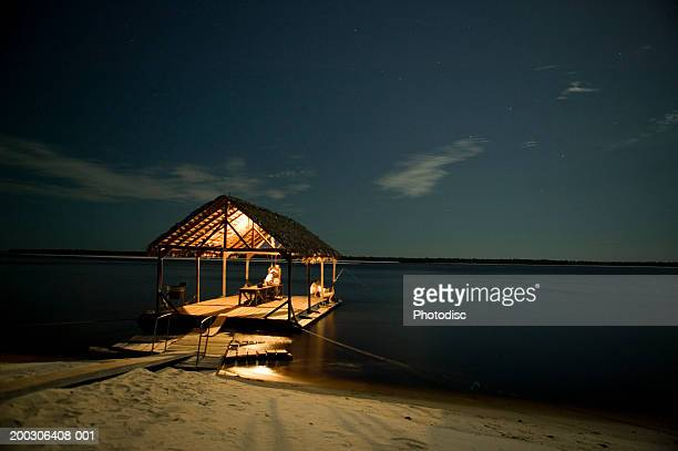 Floating hut by shore of beach at night