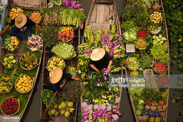 A floating market on a canal in Thailand. Boats laden with fresh produce, vegetables and fruit. Market traders.