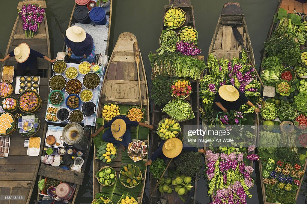 A floating market on a canal in Thailand. Boats laden with fresh produce, vegetables and fruit. Market traders. : Foto de stock