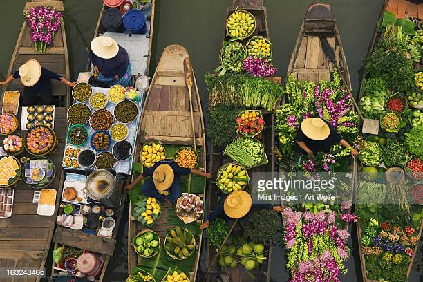 a floating market on a canal in thailand. boats laden with fresh produce, vegetables and fruit. market traders. - markt stockfoto's en -beelden