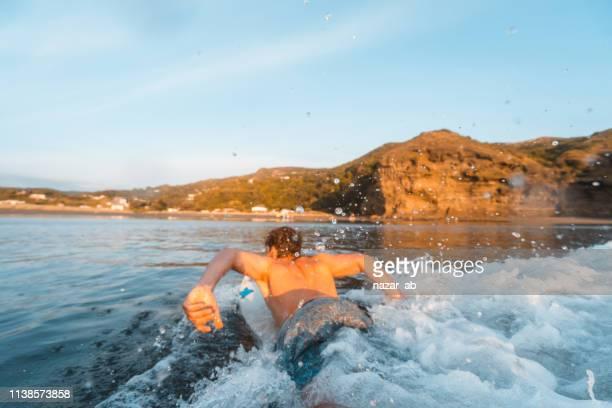 flutuando no surfboard. - só um homem jovem - fotografias e filmes do acervo