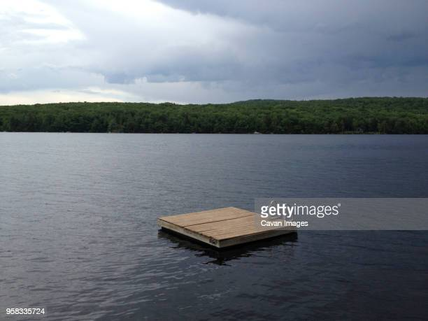 floating platform on lake against cloudy sky - diving platform stock pictures, royalty-free photos & images