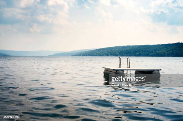 floating platform on lake against sky - diving platform stock pictures, royalty-free photos & images