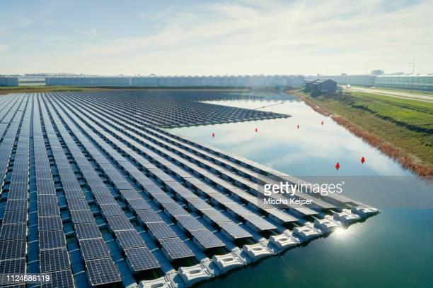 floating solar panels installed on water supply of neighbouring greenhouses, elevated view, netherlands - drijven stockfoto's en -beelden