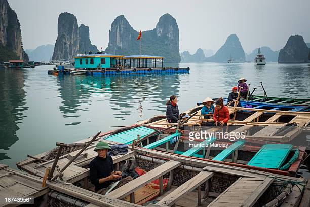 Floating village in Ha Long Bay with a fisherman sitting in a rowing boat as well as women chatting together waiting to transport tourists around the...