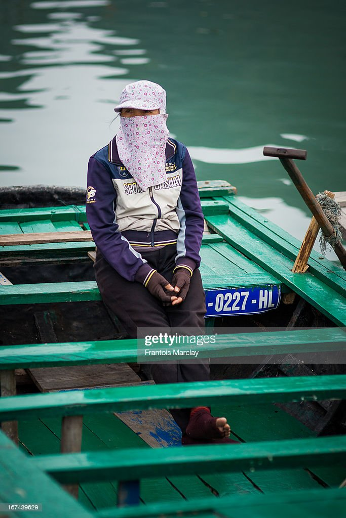 CONTENT] Floating village in Ha Long Bay with a woman sitting in a rowing boat face covered waiting to transport tourists around the islands.