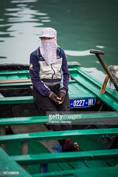 CONTENT] Floating village in Ha Long Bay with a woman sitting in a rowing boat face covered waiting to transport tourists around the islands