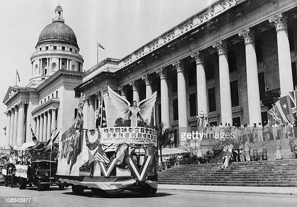 Floats in a parade marking the first anniversary of VJ Day pass the Governor Sir Franklin Gimson on the steps of the Municipal Building Singapore...