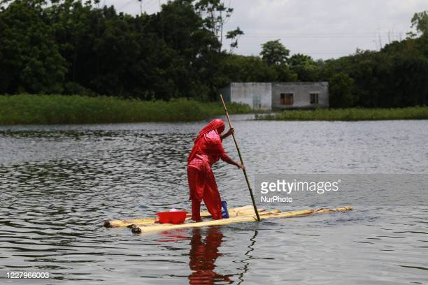 Flood affected woman rides makeshift raft in the floodwater in Keraniganj outskirts of Dhaka, Bangladesh on August 8, 2020.