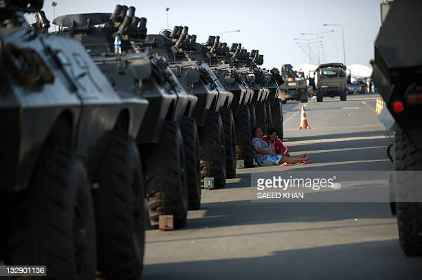Flood affectees sit in the shadows of armoured carrier vehicles parked on high ground to avoid floodwaters in the outskirts of on the outskirts of...
