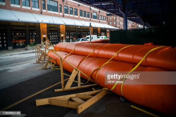 Flood barriers are set up to prevent a potential flooding at the South Street Seaport as the city gets ready for tropical storm Isaias on August 4...