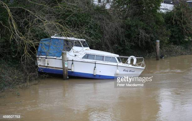 A flood damaged boat lies on the banks of the River Medway on December 27 2013 in Tonbridge England High winds and flooding are continuing to cause...