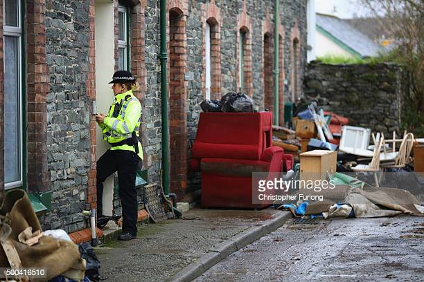 Flood damaged possessions pile up in front of homes as a police officer checks the wellbeing of residents on December 8 2015 in Keswick United...
