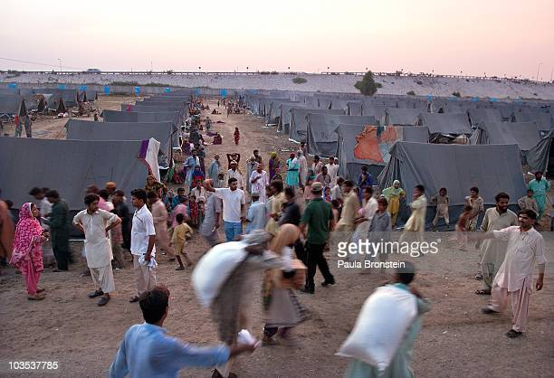 Flood survivors walk around at a crowded tented camp for victims with sacks of wheat distributed by the World Food Program on August 21 2010 in...