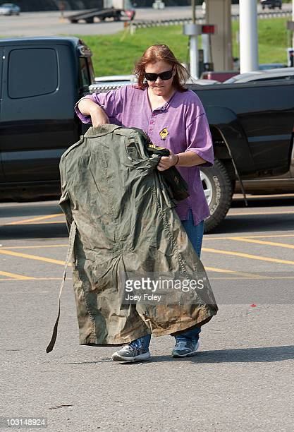 A flood victim carries a dirty soldier's uniform to the drop off area at the 'Tide Loads Of Hope' free mobile laundry services where residents...