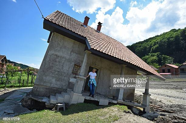 Flood victim Pavlovic Oksana stands on the front porch of her house damaged by flooding and landslide in Krupanj some 130 kilometres south west of...