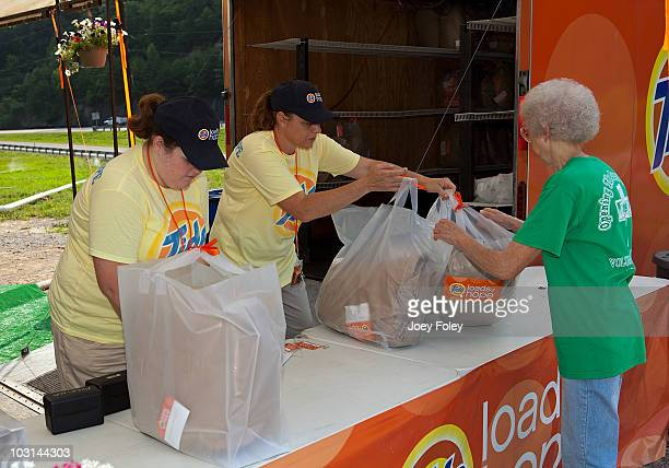 A flood victim picks up her clean laundry at the Tide's Loads Of Hope mobile laundry program at the Loads of Hope Truck Laundry DropOff Site Food...