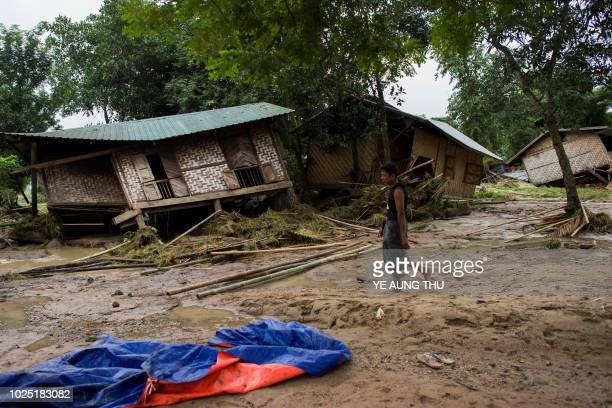 A flood victim walks pass in front of a house damaged by rampaging flood waters from Swar Chaung Dam in Swar township in Bago region on August 30...