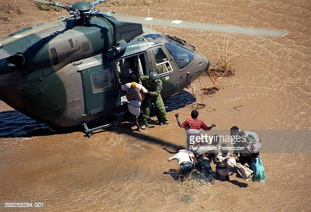 flood victims are rescued by a south african army helicopter crew in chibuto, mozambique - per-anders pettersson stock pictures, royalty-free photos & images