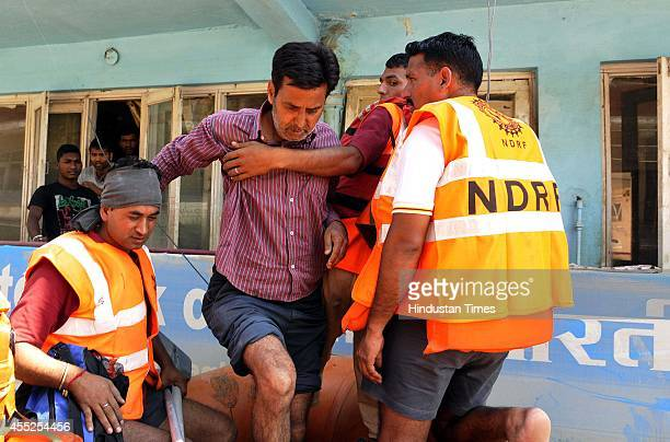 Flood victims are taken to the safer places by NDRF in a boat as their houses are submerged in flood waters on September 11 2014 in Srinagar India...