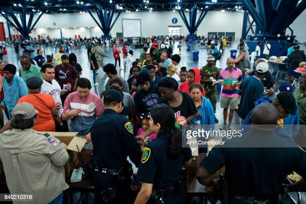 Flood victims gather for food at a shelter in the George R Brown Convention Center during the aftermath of Hurricane Harvey on August 28 2017 in...