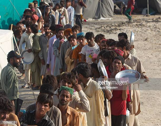 Flood victims line up for food distribution at a tented camp on August 21 2010 in Sukkur Pakistan The country's agricultural heartland has been...