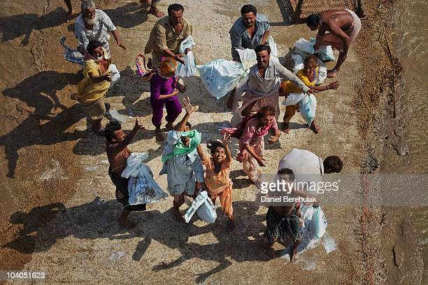Flood victims scramble for food rations dropped by Pakistan Army soldiers during relief operations on September 13 2010 near the village of Goza in...