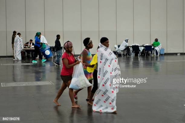 Flood victims walk through a shelter in the George R Brown Convention Center during the aftermath of Hurricane Harvey on August 28 2017 in Houston...